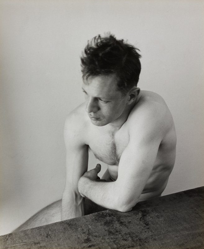 nude man resting his elbow on a table