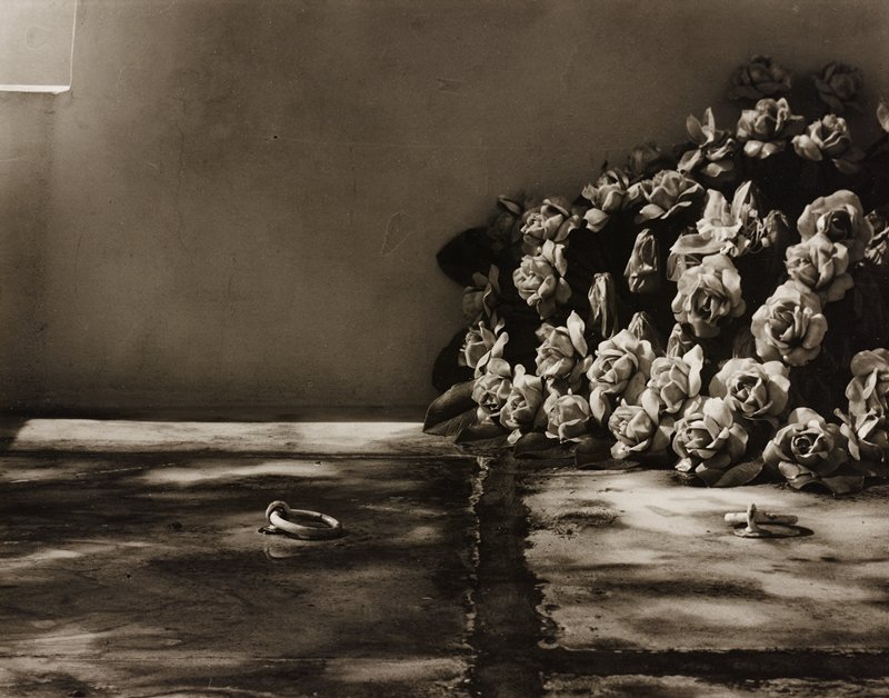 two metal rings on floor plates; large bouquet of roses at right