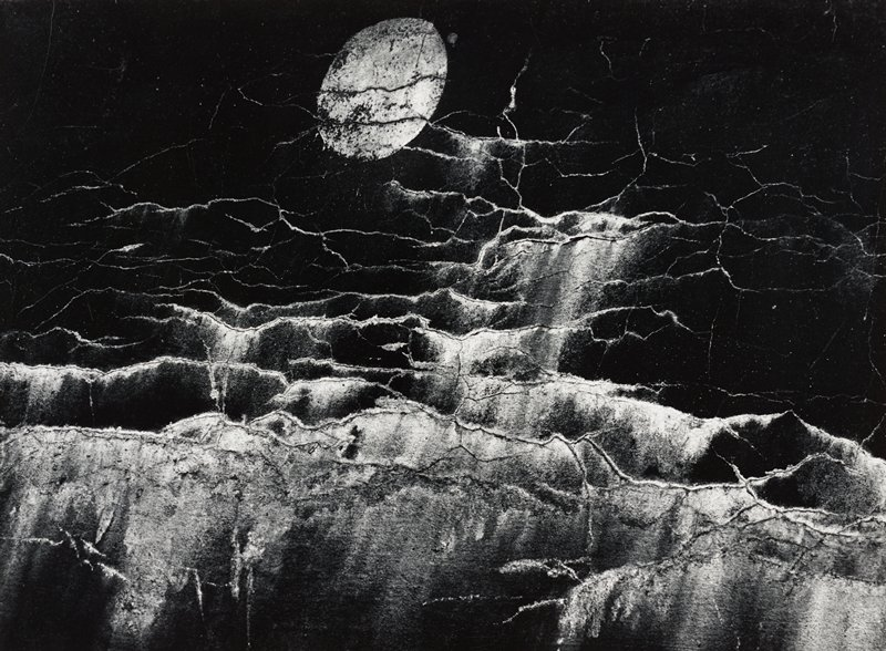 abstract image; crackling on a dark surface with vertical streaks giving the illusion of waves on water; round, light-colored element at top center looks similar to a moon