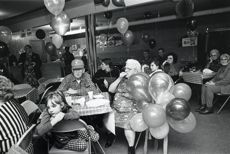 black and white photo of people sitting at tables; balloons scattered throughout room