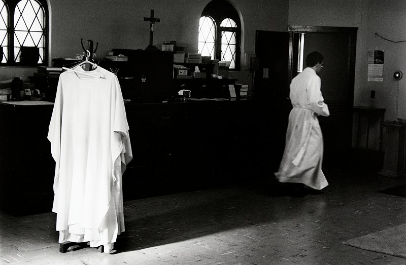 black and white photo of man in white robe walking away from camera; robes on hangers, left side of image