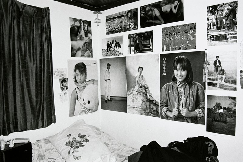 black and white photo of bedroom, posters on wall