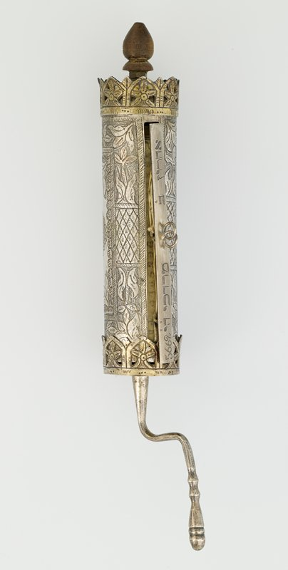 cylinder with crank-shaped handle at one end and wood finial at other end; large overall foliate and geometric decorations; double ring at opening
