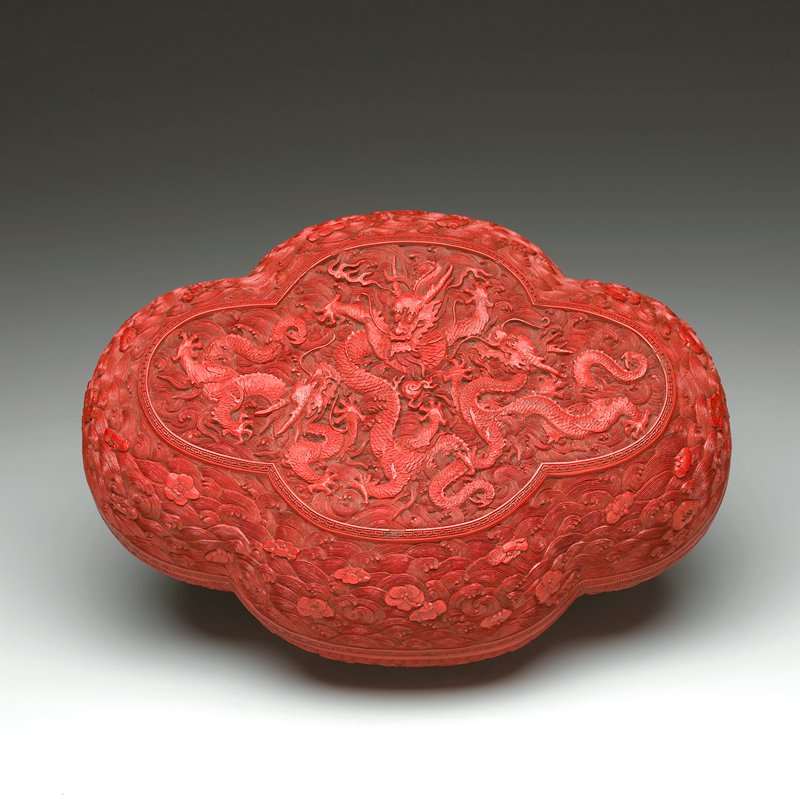 waves and flowers on sides; top carved with 3 dragons on top of waves; red lacquer; oval in shape with four lobes, rounded sides and corners