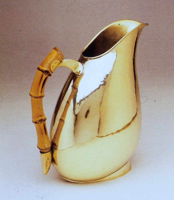 Hammered brass; ovoid vessel resting on a teardrop shaped foot; handle is mounted section of bamboo; likely executed by Hagenauer Werkstatte, Vienna