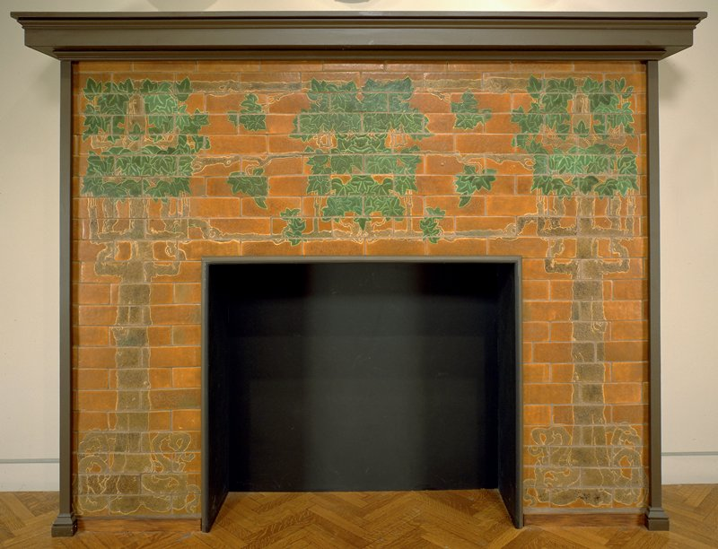 buff terracotta tiles with press-molded design, covered in green and shades of brown and rust matte glazes; framed in oak