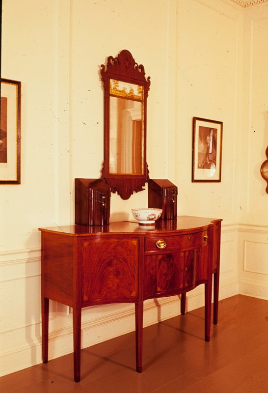sideboard, style of Hepplewhite; a central long upper drawer above two doors concealing storage space, is flanked by a door on either side; oval brasses. satinwood fan inlays at corners; six slender tapering legs, two at rear, four in front; the particular feature is the diagonal setting of the central pair of legs