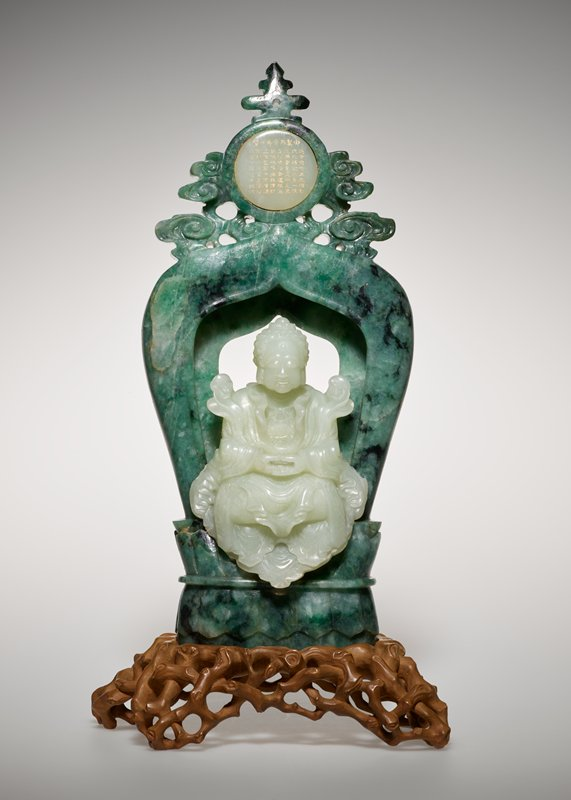 A Sino-tibetan Buddha shown seated in a muhdra of meditation, carved from white jade and with an angled ledge in the back of the figure fitting precisely onto a mottled green and black jadeite throne in the form of a Tibetan stupa, surmounted by cloud motif finial surrounding a white jade medallion with inscripotion picked out in gilding.
