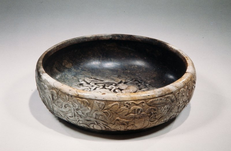 The opaque brown and cloudy tan-colored jade apparently burned in a fire, the shallow bowl with deeply rounded sides carved on the exterior and interior with butterflies and melon vine. Broken in two pieces and restored. Former Classification: Jade
