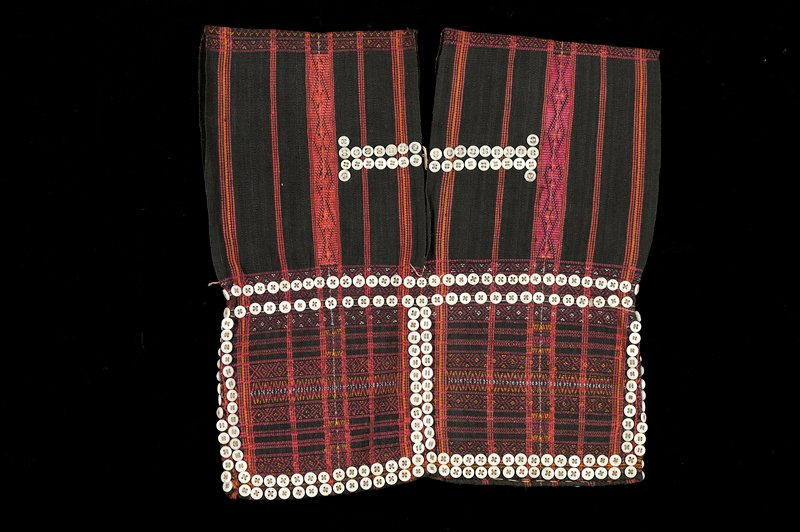 two panels stitched together at center back and underarms; decorative woven pattern and stripes in black, red, yellow and white; embellished with white buttons
