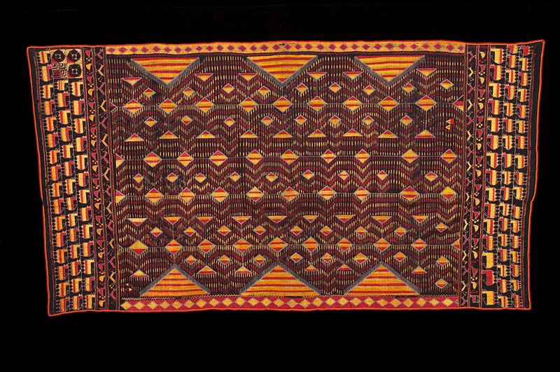 black ground, bound in red; geometric embroidery motifs in center; borders of rows of animals; embroidery in gold, red, green, white