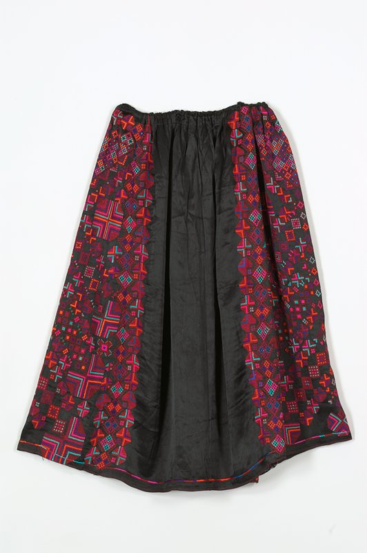 black ground with embroidered geometric pattern in rose, purple, blue, red, green, orange, turquoise