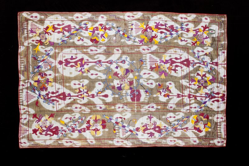 Suzani embroidery on green, red and white ikat ground; stylized motifs in white, red, blue, purple, orange, black; red polka dot binding