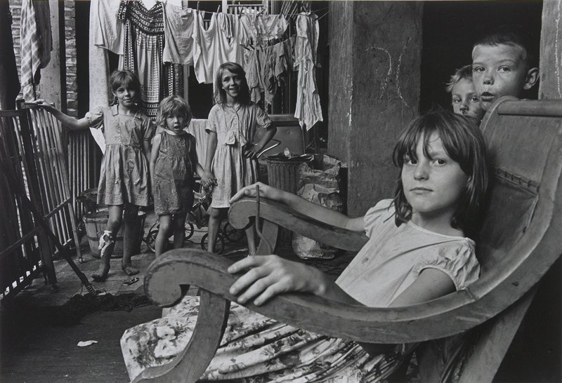 six children: girl in rocking chair in front, two boys' faces at right edge, three girls holding hands at left; laundry hanging on a clothesline behind girls