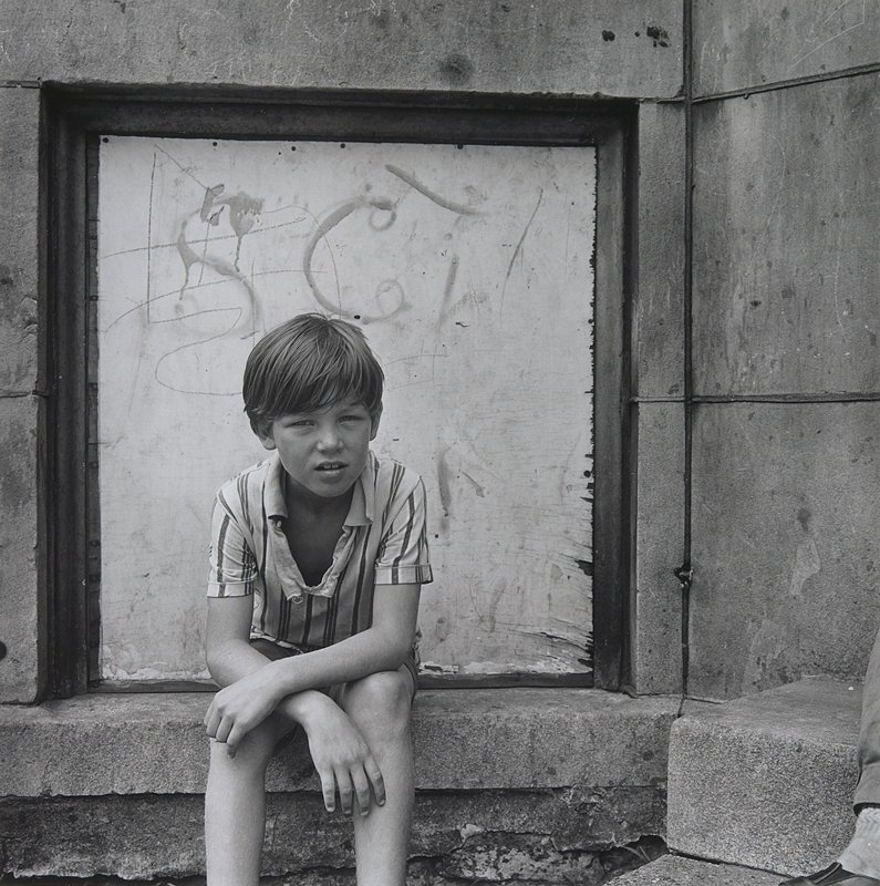 boy wearing a striped shirt, seated on a step in front of a wooden panel with grafitti