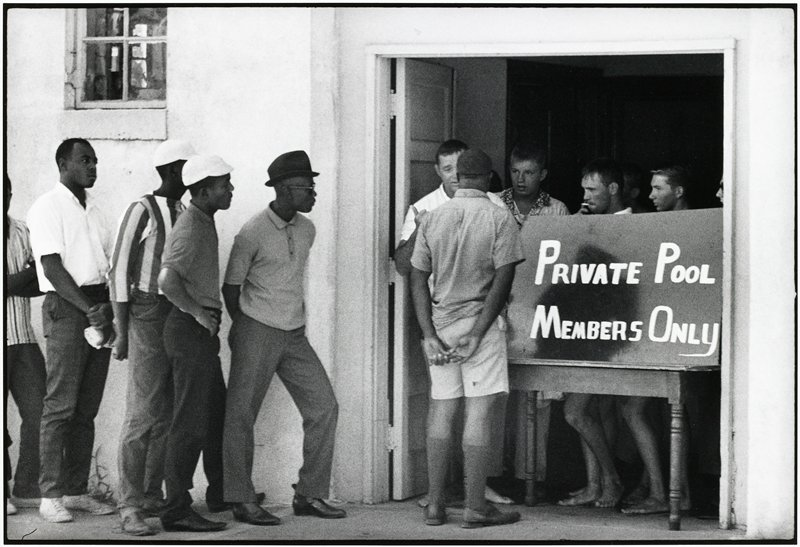 "five black men waiting in line at left, while another black man faces four white men standing inside a doorway behind a sign reading, ""Private Pool/Members Only"""