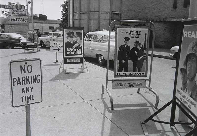 "four military recruiting signs, a No Parking sign and a sign reading ""White Waiting Room"" on the sidewalk by a curving street"