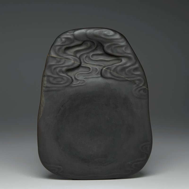 dark brown stone with tan streaks near top and on back; slightly narrower at top with swirling cloud design at top and bottom; undecorated box