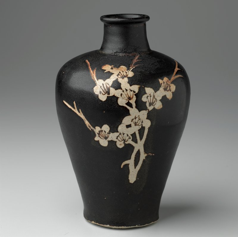 meiping shaped jar with short neck and slightly flaring lip; brown glaze with glaze resist and slip painted prunus sprays on each side