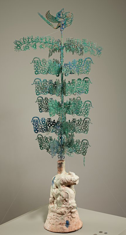 base with iridescent light green glaze and 2 animals, one standing on the back of the other; long post topped with openwork bird finial; 4 long branches at top: 3 depict figures dancing and holding objects and a figure under a canopy on top of branch and figures and radiating coins below branch; one depicts same scene except an animal replaces the figure under canopy; 20 rectangular branches, 19 with figures, horses, deer and figure under canopy with coins sprouting from branches; one with same scene except animal and figure(?) replace figure under canopy; 40 small branches with 3 radiating coins; pendant of monkey with a coin