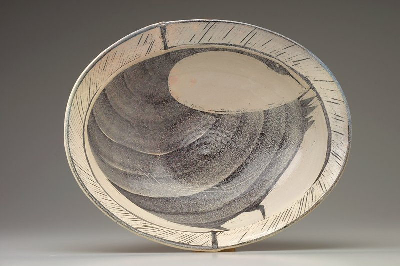 large ovoid bowl with tan exterior; white interior with a large black abstracted duck