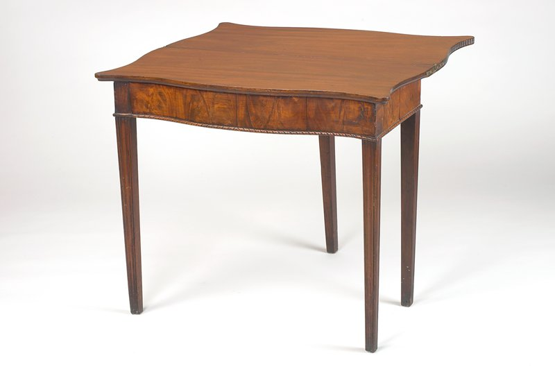 folding card table with removable drawer; tapering legs; curved front; dome-shaped notches on edges of table top; medium finish