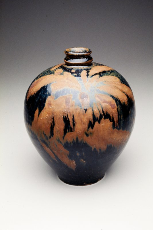 Bulbous high-shouldered form with tapering foot and narrow ribbed neck; buff body covered with glossy black glaze with faint blue iridescence.