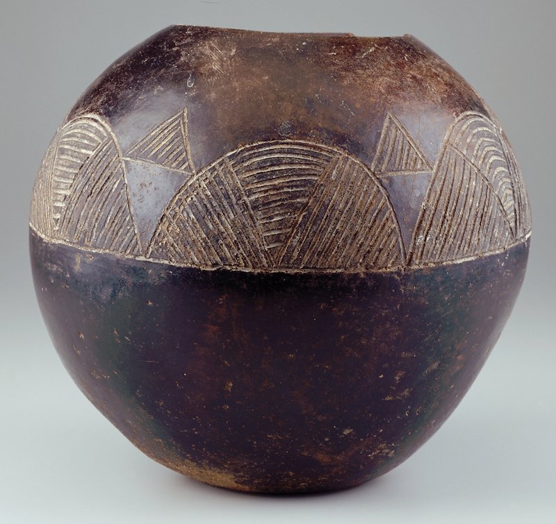 round vessel with sgraffito decoration in upper half of form; surfaces are burnished; clay body is dark chocolate brown
