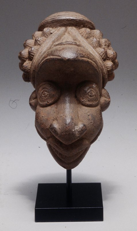 In the form of a human head; pipe is missing stem/mouth piece; head possibly is anthropomorphic with animal head above human face