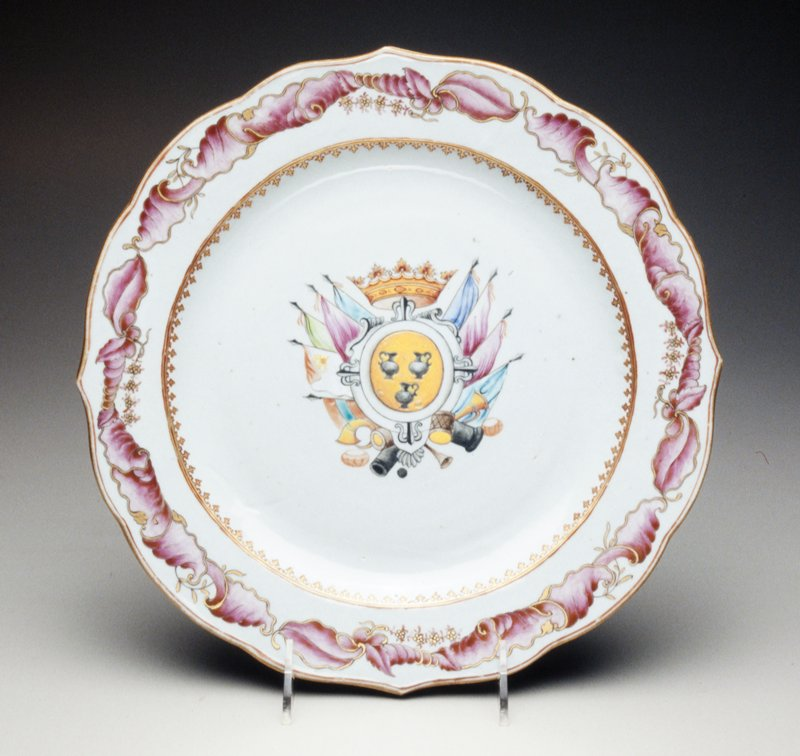 armorial plate, famille rose central coat of arms among colored flags and crown, three central urns with instruments, interior of rim with gilt spearheads; arms are those of Pignatelli of Naples, related to Antonius Pignatelli who was Pope Innocent XIII