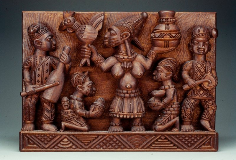 relief carving of three standing figures (2 with musical inbstruments, one with a chicken and a jug); 2 kneeling figures