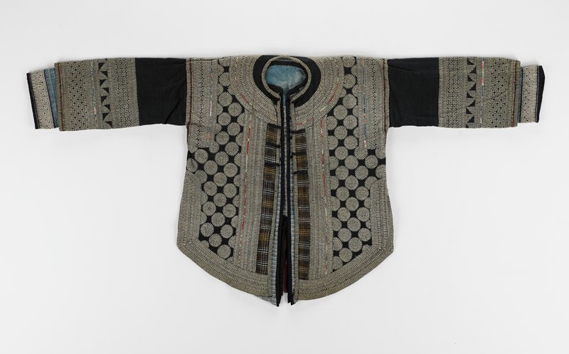 2 separate layers; outer layer batik dyed with geometric patterns; applique and green embroidered highlights overall; inner layer light and dark blue striped with batik cuffs