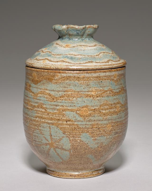 small covered vessel; domed cover with floral finial; incised designs of wavy lines and flowers; blue, brown and tan glaze with subtle orange spots; brown interior