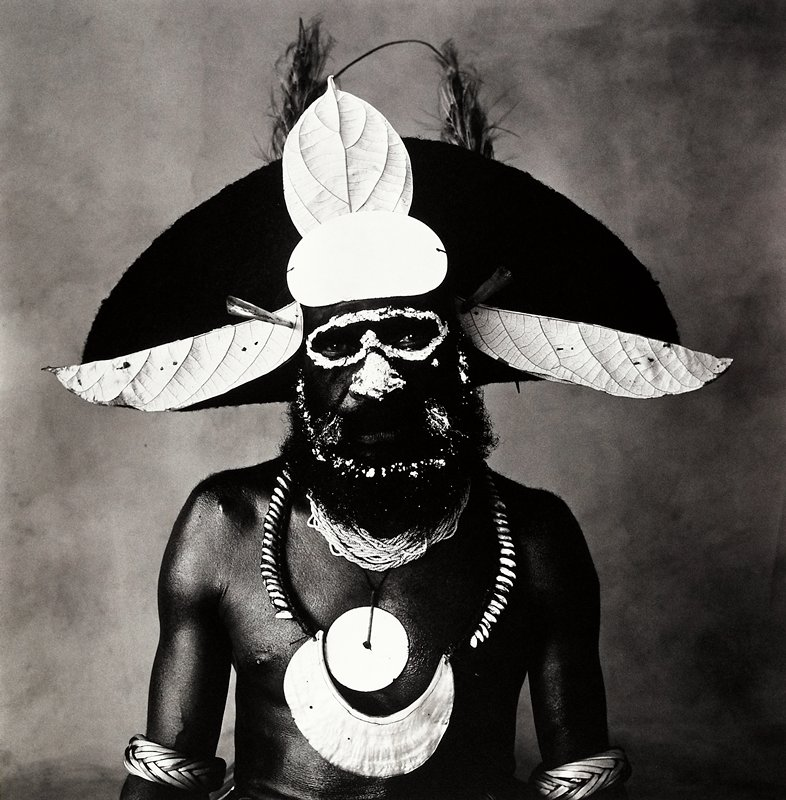 torso and head of thin black man with beard; light paint around his eyes, on his nose and on beard; wearing large headdress with leaves, necklaces and bracelets; mounted on aluminum sheet