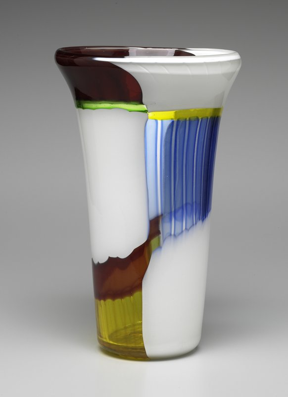 white, thick walled vase with 3 patches of color: yellow and brown at bottom, blue and yellow at center, and red and green at top