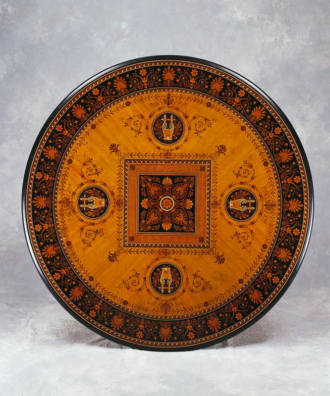 circular inlaid table with four footed pedestal base; central square organic motif with banding of meandering pattern and waves; circular design with harp and wind instruments crossed at center of each side of square; outer band of floral pattern on dark ground