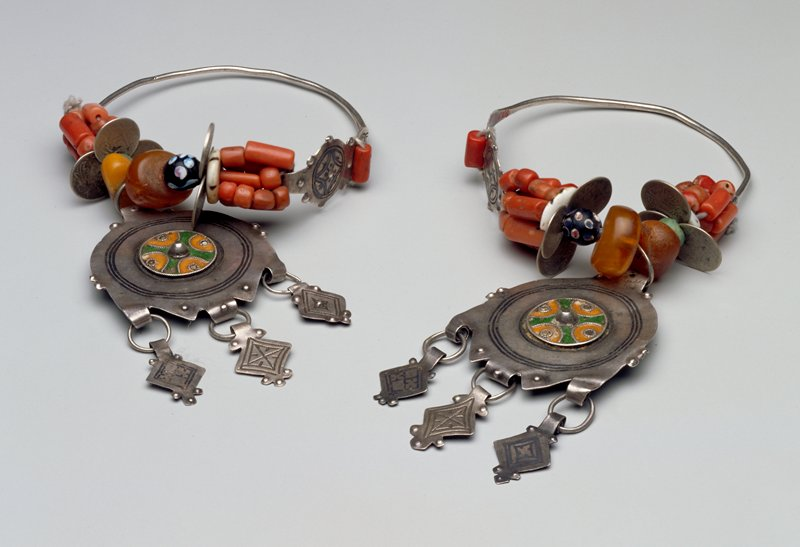 large hanger loop of metal; beads, coins and amber adorn lower loop; at bottom hangs a large circular medallion with central enameled floral design; three metal diamond shapes hang from bottom medallion