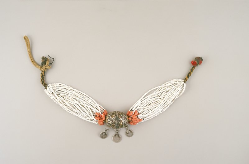 central silver ovoid broken down into four enameled bands with circle designs; three coins hang from bottom; long thin strands of white beads with orange beaded ends flank either side