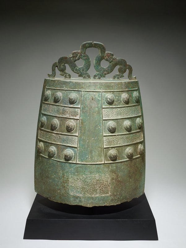bronze budhist temple bell; tall football shaped body with flat top; two dragons turned away from each other form hanger at top center; sides decorated with two rectangular fields striped with three bands of three raised circular bumps