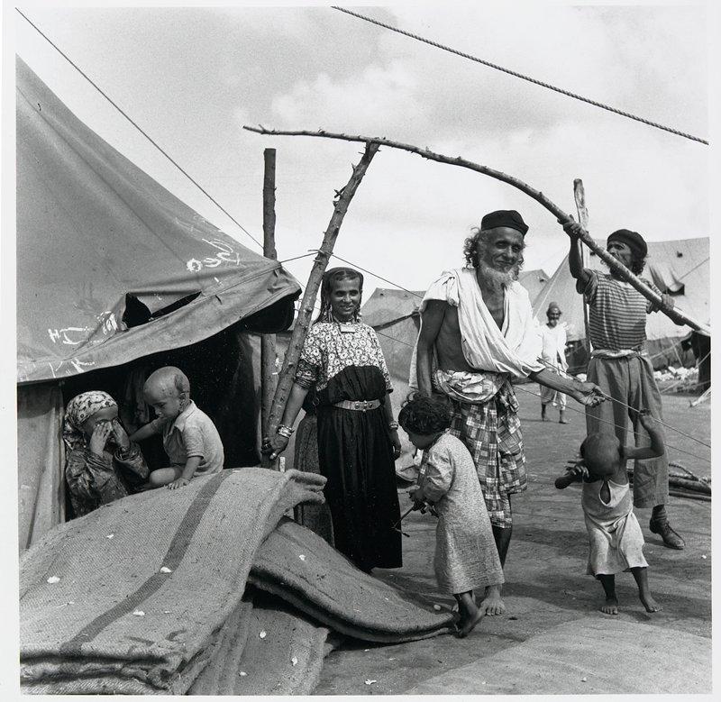 men, women and children in front of tent