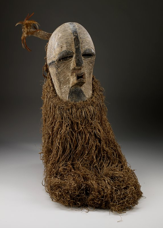 round head covered with linear decorations and black and white pigment; large, wide eyes; long, pursed lips; long plant fiber beard