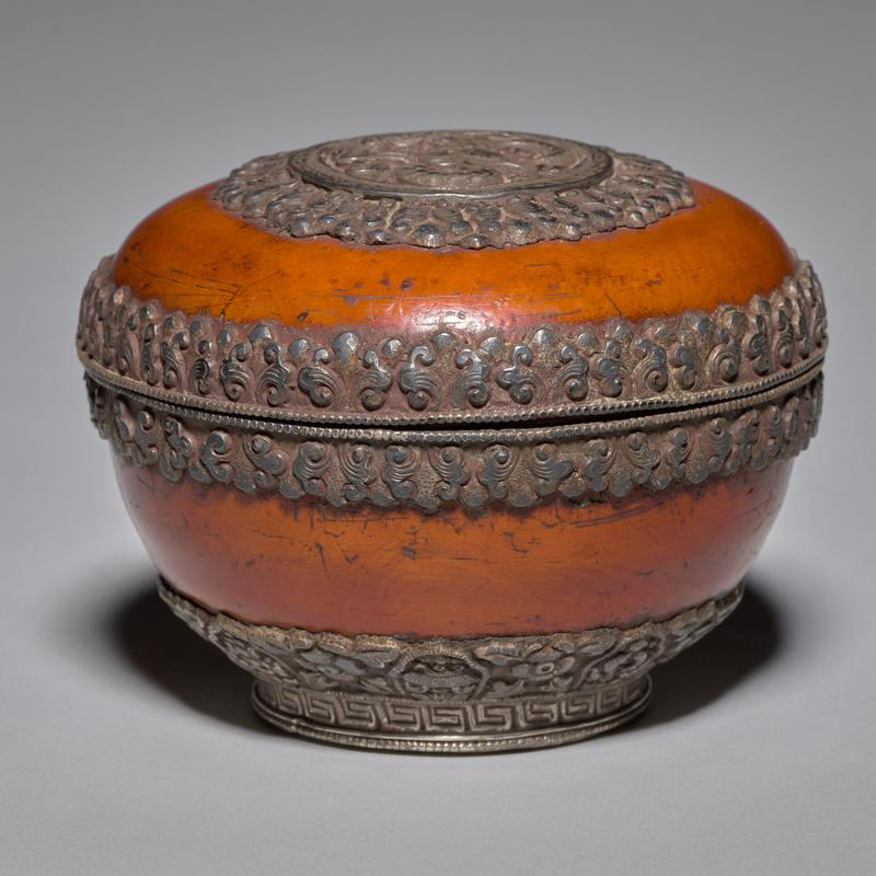 wooden covered round box with silver trim; embossed dragon in a medallion at center on top with chased floral designs around egde of medallion and edges of base and lid; floral design at bottom edge