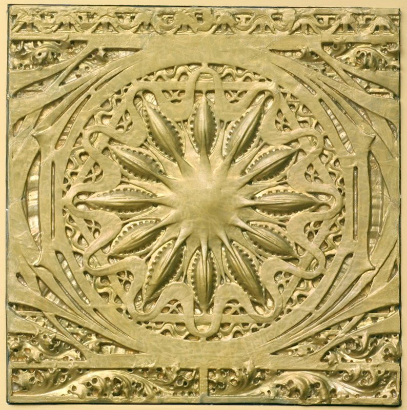 Flower-like central medallion surrounded by organic motifs; mounted to a plywood backing