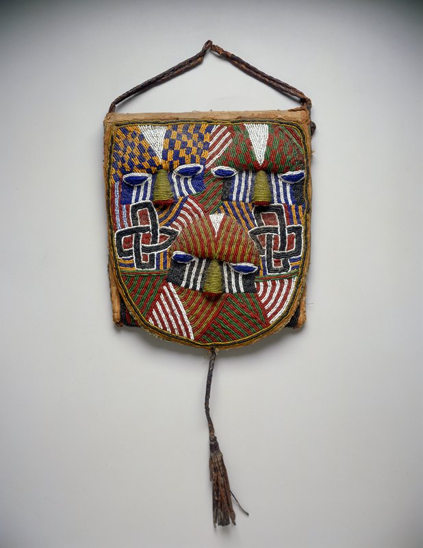 cloth pouch with front flap decorated with beads; design of three stylized faces with interlocking geometric designs; braided leather tassels and handles; attached to square black mount