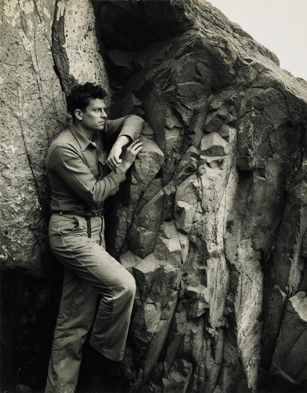 man leaning against rocks; man wears a long-sleeved shirt and pants