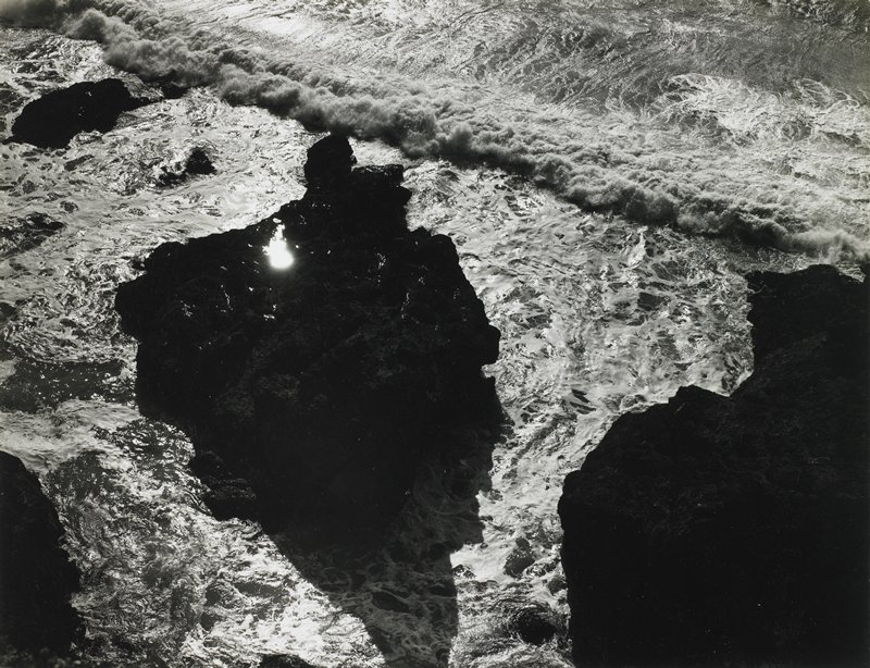 large rocks in water, seen from above, with waves