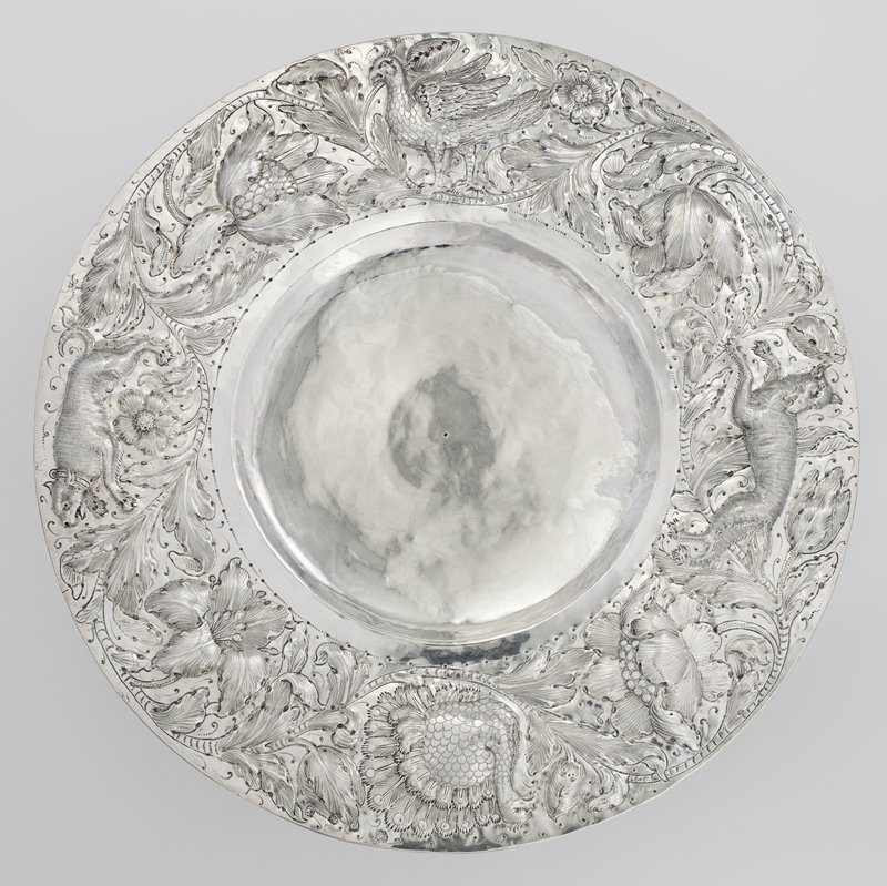 Charles II repoussé tazza; fully marked on rim and with lion passant underfoot; shallow circular dish with wide flat rim embossed in bold relief with a wolf, a boar, a turkey, and a falcon amid undulating stems of leafage and large blossoms with punchwork tendrils; on low, hollow flaring foot with flat rim