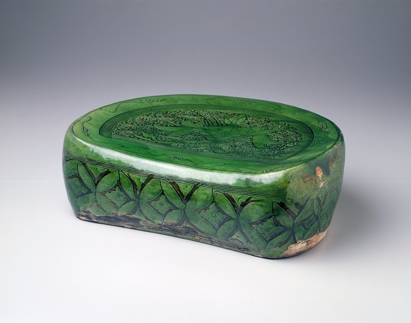 earthenware bean shaped headrest carved at center with ribbon tied spray of lotus and sagittarius blossoms against a dense ground of scrolling vines; green glaze