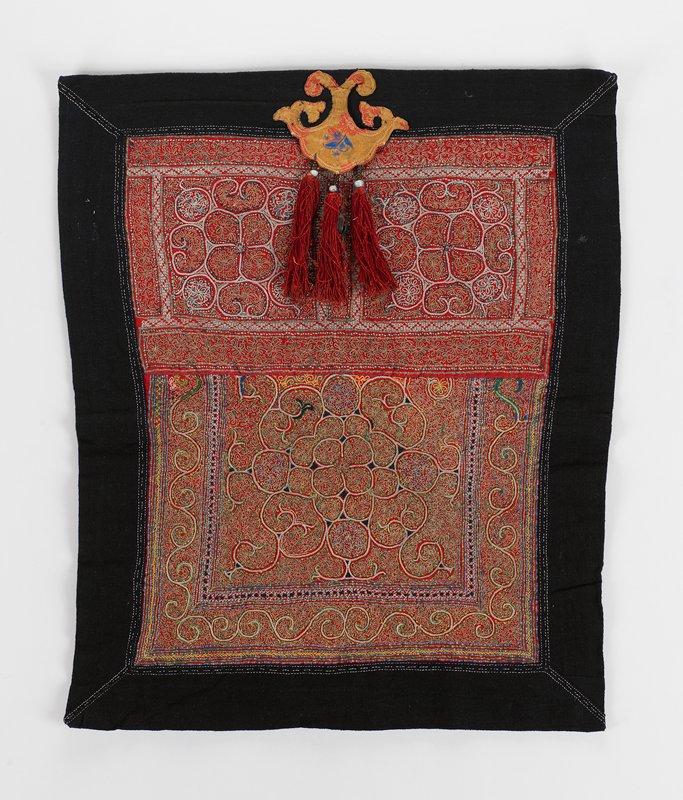dark blue backing and border; red field with multicolored scrolling embroidered designs, filled and surrounded by abstracted floral patterns; 3 tassels and hanging bell