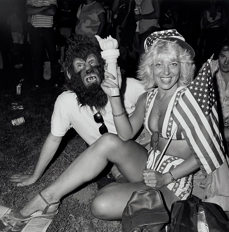 seated blonde woman holding a Lady Liberty torch flashlight in her PR hand and a small US flag in her PL hand, wearing shorts, a halter top and cap of fabric with stars and stripes pattern; man seated behind her wearing a werewolf mask; other figures standing and seated in background